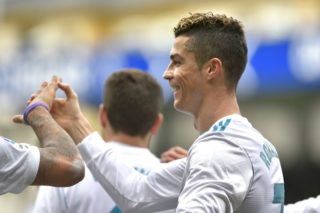 Real Madrid's Portuguese forward Cristiano Ronaldo celebrates with teammates after scoring his team's second goal during the Spanish league football match between Eibar and Real Madrid at the Ipurua stadium in Eibar on March 10, 2018. / AFP PHOTO / ANDER GILLENEA