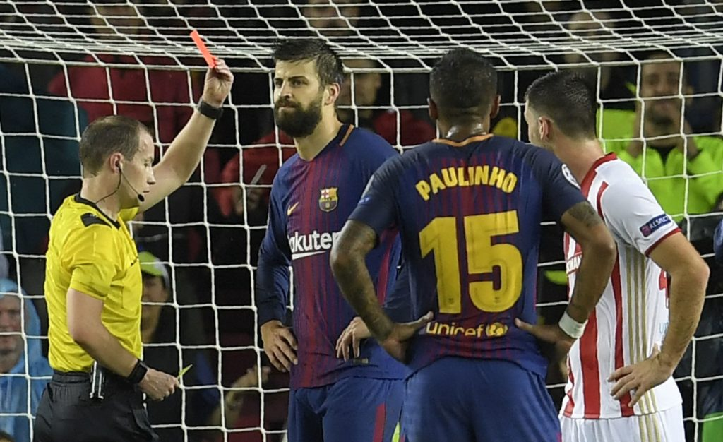 Barcelona's Spanish defender Gerard Pique (C) receives a second yellow card during the UEFA Champions League group D football match FC Barcelona vs Olympiacos FC at the Camp Nou stadium in Barcelona on Ocotber 18, 2017. / AFP PHOTO / LLUIS GENE