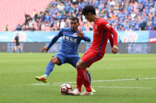 Argentine football player Carlos Tevez, left, of Shanghai Greenland Shenhua kicks the ball to make a pass against a player of Yanbian Funde in the 29th round match during the 2017 Chinese Football Association Super League (CSL) in Shanghai, China, 29 October 2017.