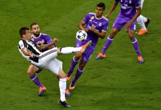 Juventus' Croatian striker Mario Mandzukic (1st-L) scores a goal during the UEFA Champions League final football match between Juventus and Real Madrid at The Principality Stadium in Cardiff, south Wales, on June 3, 2017. / AFP PHOTO / Ben STANSALL