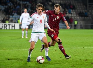 Latvia's Arturs Zjuzins (R) vies with Hungray's Adam Nagy (L) during the WC 2018 football qualification match between Latvia and Hungary in Riga on October 10, 2016.  / AFP PHOTO / Ilmars ZNOTINS