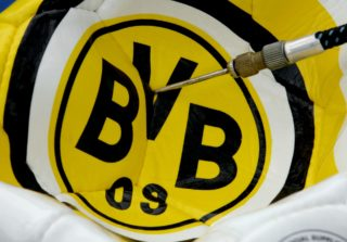 (dpa) A soccer ball bearing the logo of German Bundesliga side Borussia Dortmund receives a symbolic financial injection as it is pumped up during the shareholder meeting of Molsiris, the current leasing company and owner of the Westfalen stadium, in Duesseldorf, Germany, 14 March 2005. During the meeting it was decided to accept the reorganisation concept of the stricken Dortmund soccer club and thus save the club from insolvency. A strong majority voted to accept the club's plan to buy back parts of the stadium and also defer the rental payments for 2005 and 2006.