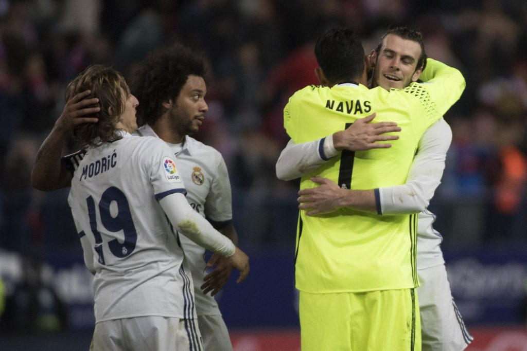Real Madrid's Welsh forward Gareth Bale (R) celebrates their victory with Real Madrid's Costa Rican goalkeeper Keylor Navas (2ndR) past Real Madrid's Croatian midfielder Luka Modric (L) and Real Madrid's Brazilian defender Marcelo at the end of the Spanish league football match Club Atletico de Madrid vs Real Madrid CF at the Vicente Calderon stadium in Madrid, on November 19, 2016. / AFP PHOTO / CURTO DE LA TORRE