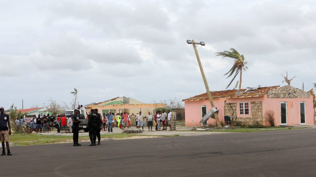 """This image provided by the Antigua & Barbuda Broadcasting Services on September 07, 2017 shows inhabitants and police officer walking beside a destroyed house on the Island of Barbuda after Hurricane Irma hit the Island. Hurricane Irma on Thursday slashed its way through the Caribbean towards the United States, transforming tropical island paradises into scenes of death and ruin. / AFP PHOTO / Antigua & Barbuda Broadcasting Services / - / RESTRICTED TO EDITORIAL USE - MANDATORY CREDIT """"AFP PHOTO / Antigua & Barbuda Broadcasting Services """" - NO MARKETING - NO ADVERTISING CAMPAIGNS - DISTRIBUTED AS A SERVICE TO CLIENTS"""