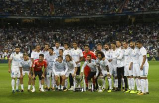 Real Madrid's players pose with the Spanish Supercup (C), the Europe Super cup (R), and the Spanish League cup before the Spanish league football match Real Madrid CF vs Valencia CF at the Santiago Bernabeu stadium in Madrid on August 27, 2017. / AFP PHOTO / CURTO DE LA TORRE