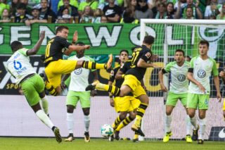 Wolfsburg's Dutch midfielder Riechedly Bazoer (L) has a shot blocked by Dortmund's midfielder Mario Goetze during the German first division Bundesliga football match Wolfsburg v Dortmund at the Volkswagen arena in Wolfsburg on August 19, 2017.   / AFP PHOTO / Odd ANDERSEN / RESTRICTIONS: DURING MATCH TIME: DFL RULES TO LIMIT THE ONLINE USAGE TO 15 PICTURES PER MATCH AND FORBID IMAGE SEQUENCES TO SIMULATE VIDEO. == RESTRICTED TO EDITORIAL USE == FOR FURTHER QUERIES PLEASE CONTACT DFL DIRECTLY AT + 49 69 650050