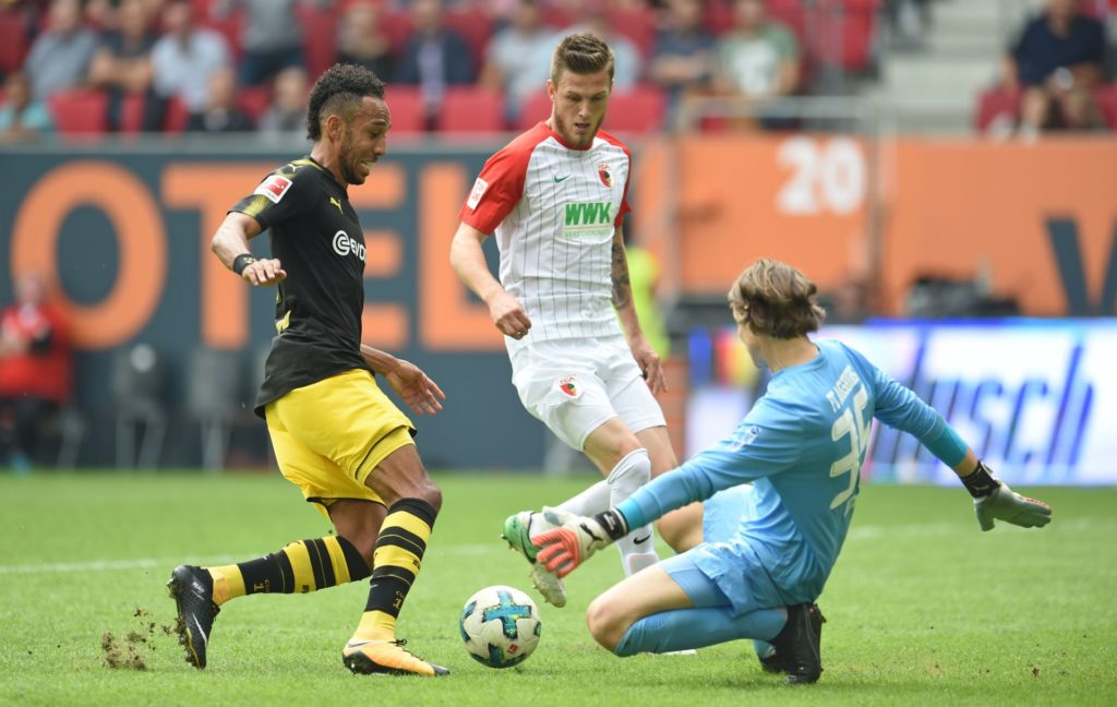Augsburg's Marwin Hitz (R) and Jeffrey Gouweleeuw and Dortmund's Pierre-Emerick Aubameyang (L)vie for the ball during the German Bundesliga match between FCAugsburg and Borussia Dortmund at the WWKArena in Augsburg, Germany, 30 September 2017.  (EMBARGO CONDITIONS - ATTENTION: Due to the accreditation guidelines, the DFL only permits the publication and utilisation of up to 15 pictures per match on the internet and in online media during the match.) Photo: Andreas Gebert/dpa