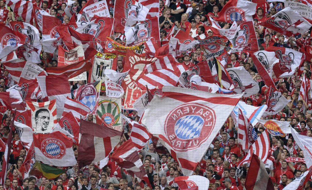 Bayern Munich fans wave the club's flags and a picture of Bayern Munich's French midfielder Franck Ribery ahead of the German first division Bundesliga football match Bayern Munich vs Hannover 96 in Munich, southern Germany, on September 14, 2013. Bayern munich won 2-0.   AFP PHOTO / CHRISTOF STACHE  RESTRICTIONS - DFL RULES TO LIMIT THE ONLINE USAGE DURING MATCH TIME TO 15 PICTURES PER MATCH. FOR FURTHER QUERIES PLEASE CONTACT DFL DIRECTLY AT + 49 69 650050. / AFP PHOTO / CHRISTOF STACHE