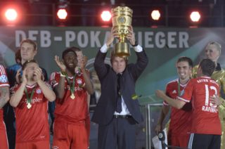 Bayern Munich's head coach Jupp Heynckes (C) holds the trophy while celebrating with his players after they won the final football match of the German Cup (DFB - Pokal) FC Bayern Munich vs VfB Stuttgart on June 1, 2013 at the Olympic Stadium in Berlin. Champions League winners Bayern Munich became the first Bundesliga champion to win the treble after their hard-earned 3-2 win over plucky VfB Stuttgart in Saturday's German Cup final. AFP PHOTO / CHRISTOF STACHE  RESTRICTIONS / EMBARGO - DFL LIMITS THE USE OF IMAGES ON THE INTERNET TO 15 PICTURES (NO VIDEO-LIKE SEQUENCES) DURING THE MATCH AND PROHIBITS MOBILE (MMS) USE DURING AND FOR FURTHER TWO HOURS AFTER THE MATCH. FOR MORE INFORMATION CONTACT DFL / AFP PHOTO / CHRISTOF STACHE