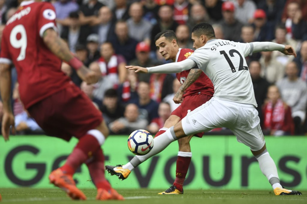 Liverpool's Brazilian midfielder Philippe Coutinho (C) shoots unsuccessfully past Manchester United's English defender Chris Smalling (R) during the English Premier League football match between Liverpool and Manchester United at Anfield in Liverpool, north west England on October 14, 2017. / AFP PHOTO / Paul ELLIS / RESTRICTED TO EDITORIAL USE. No use with unauthorized audio, video, data, fixture lists, club/league logos or 'live' services. Online in-match use limited to 75 images, no video emulation. No use in betting, games or single club/league/player publications.  /