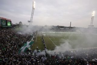 TO GO WITH AFP STORY BY PETER MURPHY  This picture taken on March 10, 2013 shows fans cheer and smoke rise during the soccer match of Hungarian football clubs Ferencvaros vs Ujpest at the Florian Albert Stadium in Budapest, Hungary, prior to its demolition. A new arena will be build to host 22,500 fans as of 2014. AFP PHOTO / PETER KOHALMI / AFP PHOTO / PETER KOHALMI