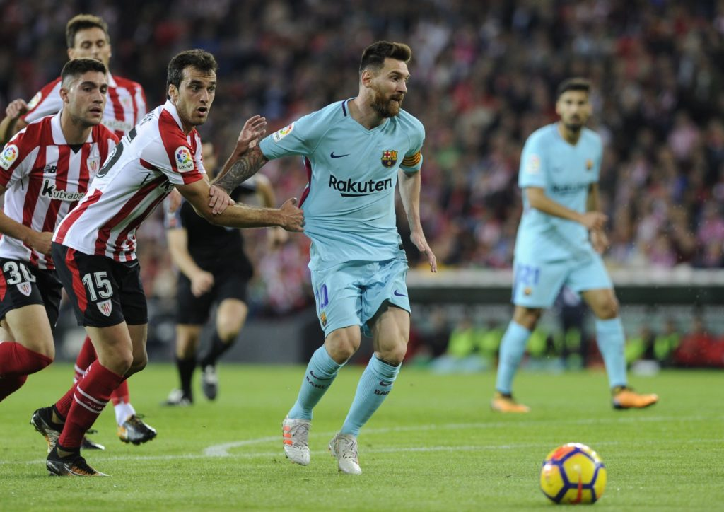 Athletic Bilbao's Spanish defender Inigo Lekue (L) vies with Barcelona's Argentinian forward Lionel Messi during the Spanish league football match Athletic Club Bilbao vs FC Barcelona at the San Mames stadium in Bilbao on October 28, 2017. / AFP PHOTO / ANDER GILLENEA