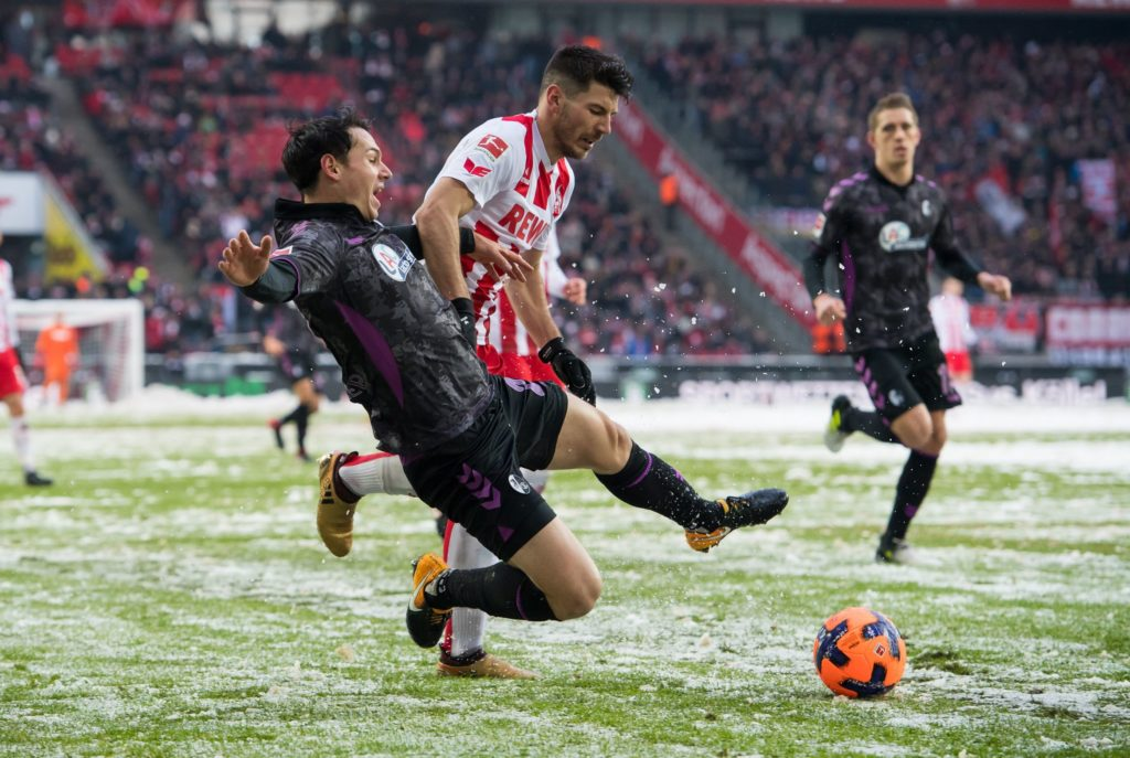 Freiburg's Nicolas Hofler (L) and Cologne's Milos Jojic vying for the ball during the German Bundesliga soccer match between 1. FC Cologne and SC Freiburg in the RheinEnergie Stadium in Cologne, Germany, 10 December 2017. The game kicked off 15 minutes later than planned due to the weather conditions.  ATTENTION: Based on the DFL's accreditation provisions, publication and further utilization on the Internet and in online media during the game is capped at a total of 15 pictures per game. Photo: Guido Kirchner/dpa