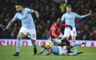 Liverpool's Spanish defender Alberto Moreno (floor) tackles Manchester United's Belgian striker Romelu Lukaku (C top) during the English Premier League football match between Manchester United and Manchester City at Old Trafford in Manchester, north west England, on December 10, 2017. / AFP PHOTO / Oli SCARFF / RESTRICTED TO EDITORIAL USE. No use with unauthorized audio, video, data, fixture lists, club/league logos or 'live' services. Online in-match use limited to 75 images, no video emulation. No use in betting, games or single club/league/player publications.  /