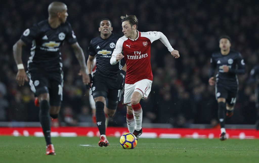 Arsenal's German midfielder Mesut Ozil (C) runs away from Manchester United's English defender Chris Smalling during the English Premier League football match between Arsenal and Manchester United at the Emirates Stadium in London on December 2, 2017.  Manchester United won 3-1. / AFP PHOTO / Adrian DENNIS / RESTRICTED TO EDITORIAL USE. No use with unauthorized audio, video, data, fixture lists, club/league logos or 'live' services. Online in-match use limited to 75 images, no video emulation. No use in betting, games or single club/league/player publications.  /