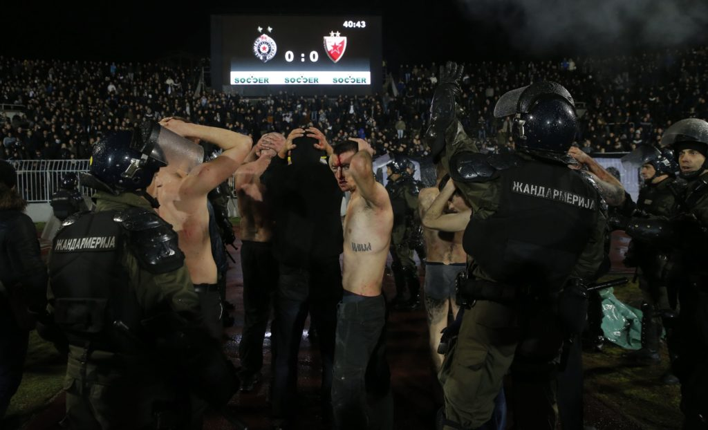 """Policemen arrest Partizan Belgrade's hooligans after clashes between two groups of Partizan Belgrade's supporters during the Serbian Superleague derby football match between Partizan Belgrade and Crvena Zvezda (Red Star), on December 13, 2017 in Belgrade. / AFP PHOTO / PEDJA MILOSAVLJEVIC / """"The erroneous mention appearing in the metadata of this photo by PEDJA MILOSAVLJEVIC has been modified in AFP systems in the following manner: [Policemen evacuate Partizan Belgrade's hooligans after clashes between two groups of Partizan Belgrade's supporters] instead of [Policemen evacuate Red star Belgrade's and Partizan Belgrade's hooligans after clashes]. Please immediately remove the erroneous mention[s] from all your online services and delete it from your servers. If you have been authorized by AFP to distribute it to third parties, please ensure that the same actions are carried out by them. Failure to promptly comply with these instructions will entail liability on your part for any continued or post notification usage. Therefore we thank you very much for all your attention and prompt action. We are sorry for the inconvenience this notification may cause and remain at your disposal for any further information you may require."""""""