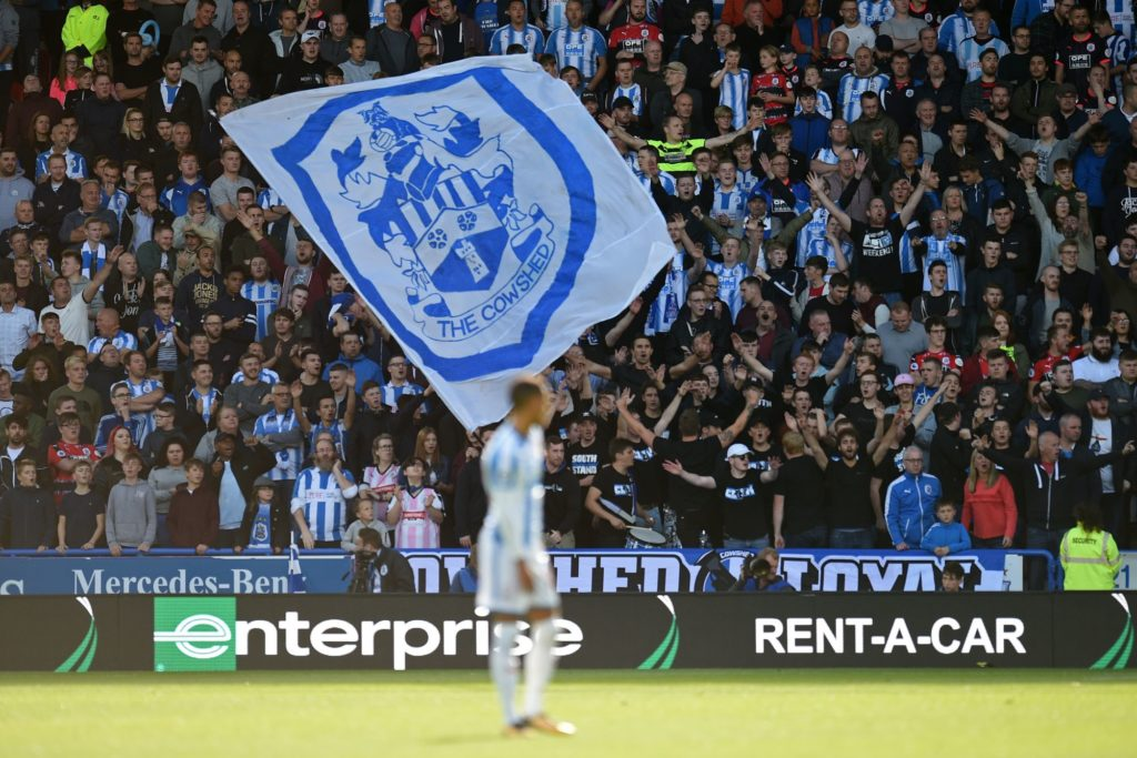 Huddersfield fans cheer on their team during the English Premier League football match between Huddersfield Town and Leicester City at the John Smith's stadium in Huddersfield, northern England on September 16, 2017. / AFP PHOTO / Oli SCARFF / RESTRICTED TO EDITORIAL USE. No use with unauthorized audio, video, data, fixture lists, club/league logos or 'live' services. Online in-match use limited to 75 images, no video emulation. No use in betting, games or single club/league/player publications.  /