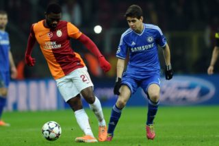 Chelsea's Oscar (R) vies for the ball with Galatasaray's Emmanuel Eboue during the UEFA Champions League round of 16 football match between Galatasaray and Chelsea on February 26, 2014 at the TT Arena Stadium in Istanbul.  AFP PHOTO / OZAN KOSE / AFP PHOTO / OZAN KOSE