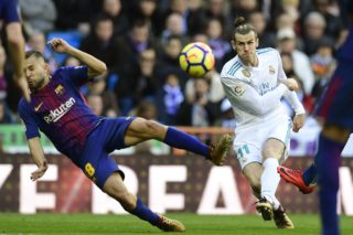 """Barcelona's Spanish defender Jordi Alba (L) veis with Real Madrid's Welsh forward Gareth Bale during the Spanish League """"Clasico"""" football match Real Madrid CF vs FC Barcelona at the Santiago Bernabeu stadium in Madrid on December 23, 2017.  / AFP PHOTO / JAVIER SORIANO"""