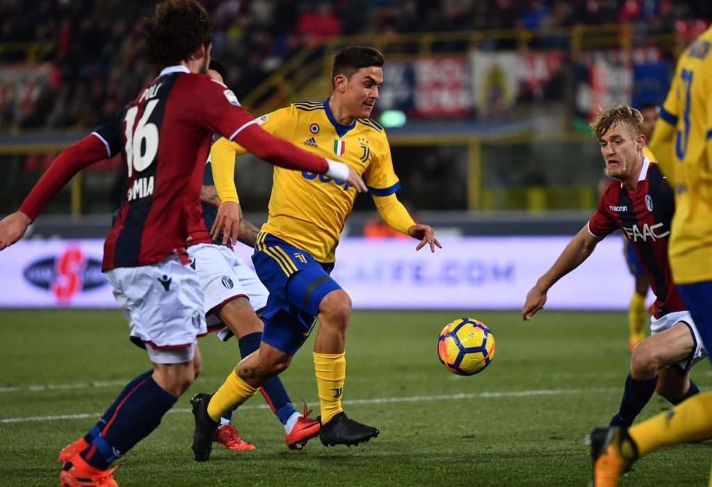 Juventus's forward from Argentina Paulo Dybala (C) fights for the ball with Bologna's midfielder Andrea Poli during the Italian Serie A football match Bologna vs Juventus on December 17, 2017 at Renato Dall'Ara stadium in Bologna.  / AFP PHOTO / ALBERTO PIZZOLI