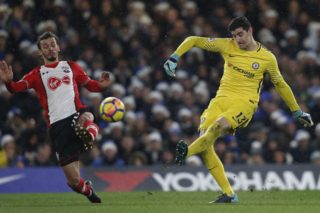 Chelsea's Belgian goalkeeper Thibaut Courtois (R) kicks the ball past Southampton's Italian striker Manolo Gabbiadini during the English Premier League football match between Chelsea and Southampton at Stamford Bridge in London on December 16, 2017. / AFP PHOTO / Adrian DENNIS / RESTRICTED TO EDITORIAL USE. No use with unauthorized audio, video, data, fixture lists, club/league logos or 'live' services. Online in-match use limited to 75 images, no video emulation. No use in betting, games or single club/league/player publications.  /
