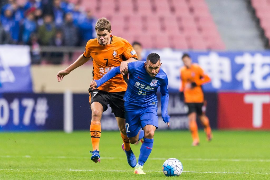 SHANGHAI, CHINA - FEBRUARY 08: Carlos Tevez (r) of Shanghai Shenhua FC competes for the ball with Thomas Kristensen of Brisbane Roar during their AFC Champions League 2017 Playoff Stage match between Shanghai Shenhua FC (CHN) and Brisbane Roar (AUS) at the Hongkou Stadium, on 08 February 2017 in Shanghai, China. (Photo by Power Sport Images/Getty Images)