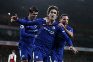 Chelsea's Spanish defender Marcos Alonso (C) celebrates after scoring with Chelsea's English midfielder Danny Drinkwater (R) during the English Premier League football match between Arsenal and Chelsea at the Emirates Stadium in London on January 3, 2018.  / AFP PHOTO / Ian KINGTON / RESTRICTED TO EDITORIAL USE. No use with unauthorized audio, video, data, fixture lists, club/league logos or 'live' services. Online in-match use limited to 75 images, no video emulation. No use in betting, games or single club/league/player publications.  /