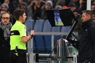Referee Gianluca Rocchi checks the Video assistant referee (VAR) during the Italian Serie A football match AS Roma vs Lazio on November 18, 2017 at the Olympic stadium in Rome.  / AFP PHOTO / Vincenzo PINTO