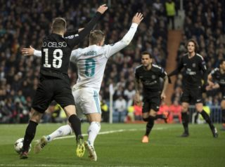 Paris Saint-Germain's Argentinian midfielder Giovani Lo Celso (L) tackles Real Madrid's German midfielder Toni Kroos (R) leading to a penalty during the UEFA Champions League round of sixteen first leg football match Real Madrid CF against Paris Saint-Germain (PSG) at the Santiago Bernabeu stadium in Madrid on February 14, 2018.   / AFP PHOTO / CURTO DE LA TORRE