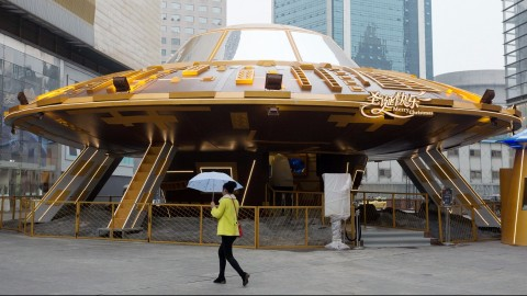 A pedestrian walks past a UFO-shaped hi-tech experience center set up to celebrate upcoming Christmas at Deji Plaza in Nanjing city, east China's Jiangsu province, 19 November 2015.  Though it is still one month earlier for people to celebrate Christmas, Chinese merchants and shopping mall operators are already gearing up to prepare for the most popular Western holiday. A giant UFO was set up along with a metallic alien to amuse passers-by on the square at Deji Plaza in Nanjing, capital of east China's Jiangsu province. Equipped with VR (virtual reality) systems, the UFO is used as a hi-tech experience center to offer virtual space travels to visitors as a new method of celebration for upcoming Christmas.